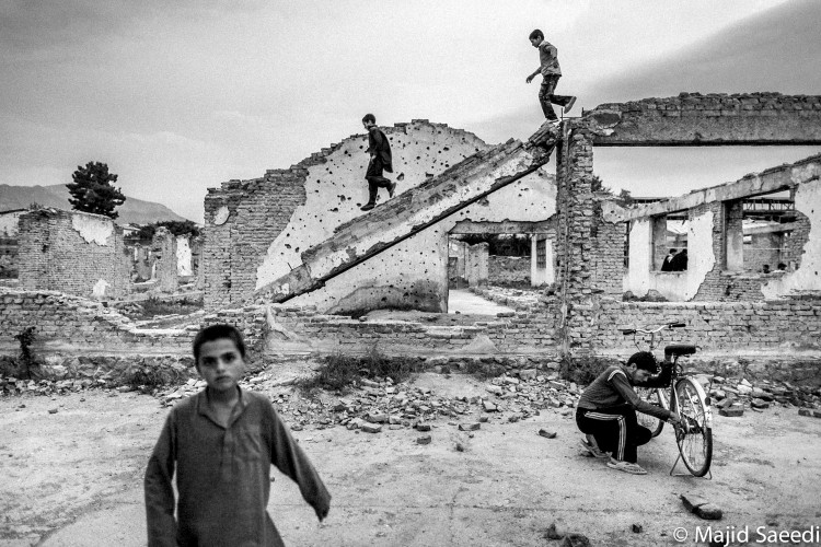 Afghan boys play in the ruins from war in center of Kabul