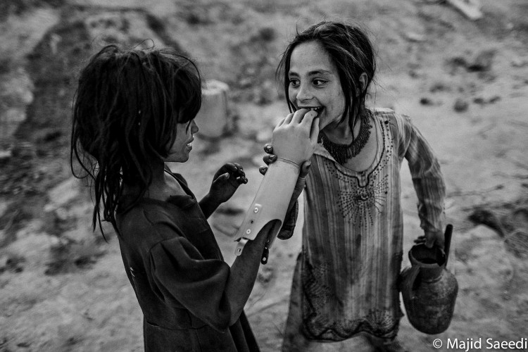 Two Afghan girls play with an artificial hand, south of Kabul